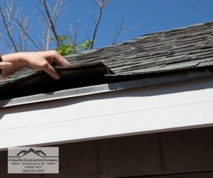 Contractor inspecting roof shingles by hand